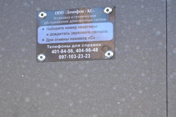 Табличка рядом с вызывной панелью с контактными данными компании по обслуживании домофонов